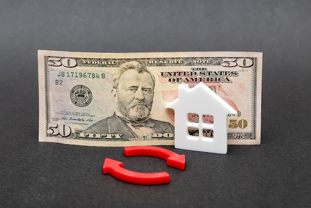 Real estate value growth. real estate market, home insurance, mortgage interest rise, fifty dollar bill on black