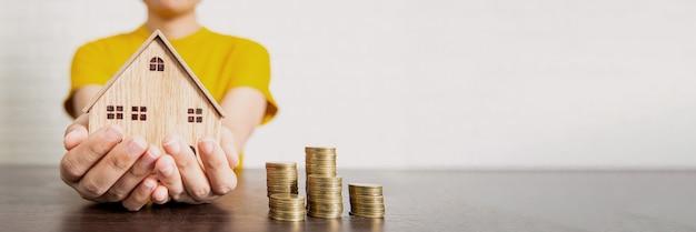 Недвижимость, женщина, держащая дом и деньги на столе, предложение пари и концепция низкого интереса