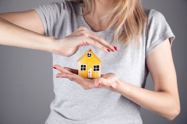 Real estate, woman holding wooden house model