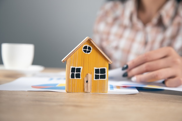 Real estate, woman working in document with house model