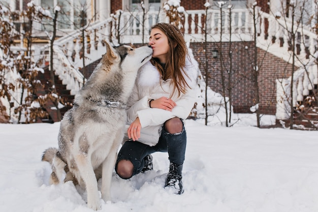 Настоящая дружба, прекрасные счастливые моменты очаровательной молодой женщины с милой хриплой собакой, наслаждающейся холодной зимой на улице, полной снега. лучшие друзья, животные любят, настоящие эмоции, поцеловали.