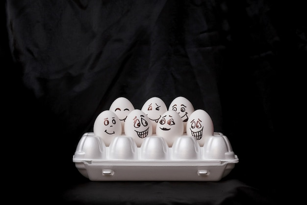 Real hand-painted eggs.  white eggs with faces drawn arranged in carton.