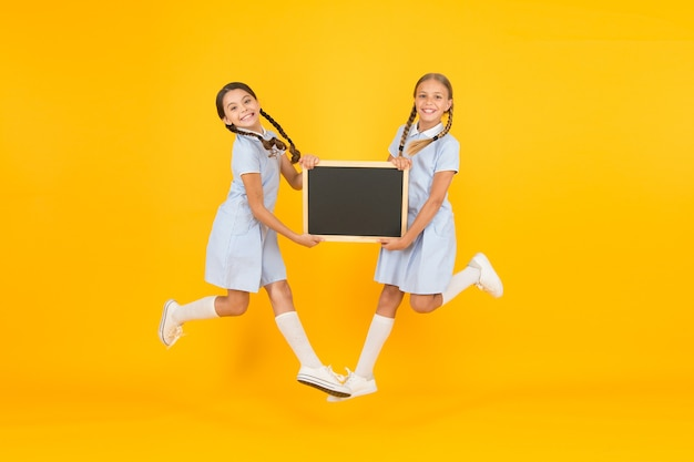 진정한 행복. 작은 소녀들은 칠판으로 점프합니다. 어린이 교육. 정보를 제시하는 작은 소녀. 오래된 학교. 보드에 공간을 복사합니다. 복고 제복을 입은 행복한 친구들. 빈티지 키즈 패션. 학교로 돌아가다.