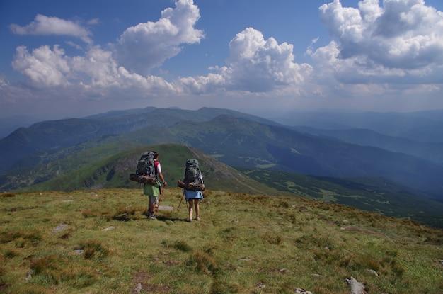 봄 또는 여름 돌과 잔디의 산 파노라마 트레일에 배낭을 메고 있는 실제 등산객