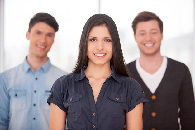 Настоящий лидер. привлекательная молодая женщина улыбается, пока двое мужчин стоят за ней