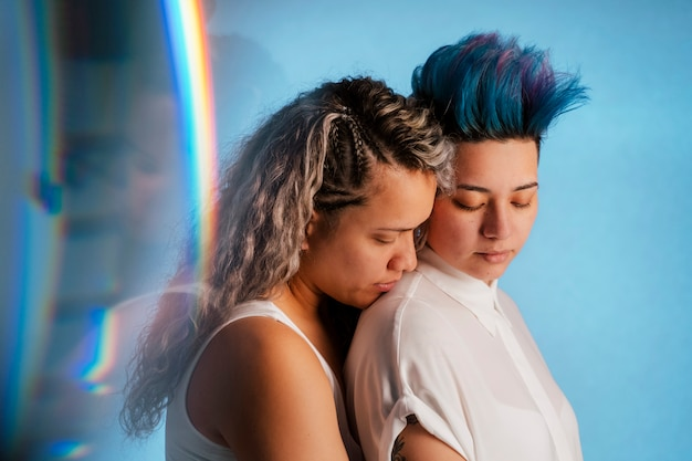 Real lesbian couple hugging with an iconic rainbow lgbt symbol. ethnic homosexual young woman about to kiss a beautiful punk woman with blue mohawk hairdo.