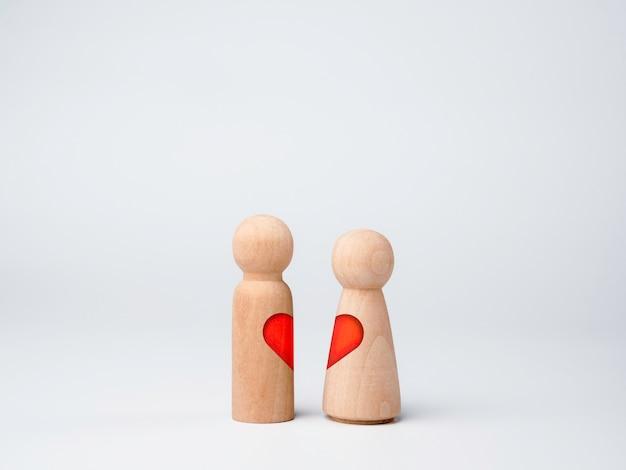 진정한 사랑, 연인, 커플 개념입니다. 몸에 붉은 심장 모양을 가진 두 개의 나무 인물이 흰색 배경에 격리되어 함께 서 있습니다.