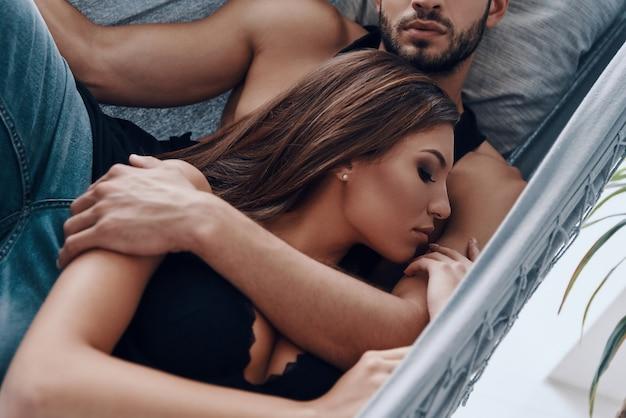 Реальная любовь. вид сверху красивой молодой пары, обнимающейся во время сна в гамаке в помещении