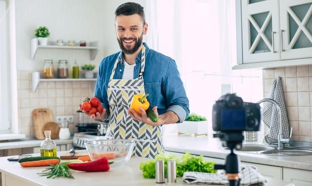 남자가 카메라에서 신선한 건강한 비건 샐러드를 요리하는 동안 집에서 진짜 남자 부엌 블로그