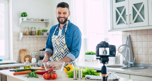 남자가 신선한 건강한 비건 샐러드를 요리하는 동안 집에서 진짜 남자 부엌 블로그