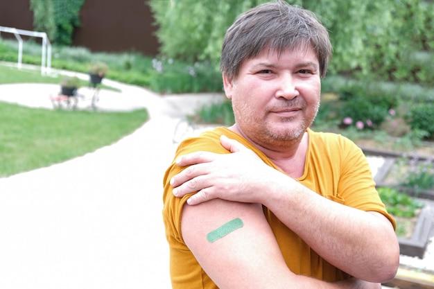 コロナウイルス感染症の予防接種を受けた本物の中年男性。 covid-19に対するワクチン接種。スプートニクvスペースをコピーします。