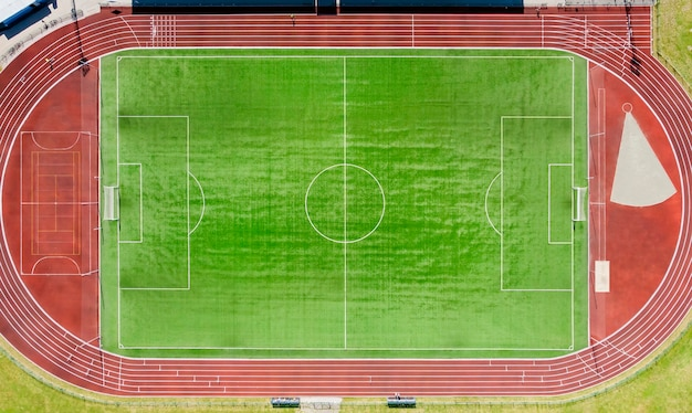 A real new soccer field, football field. green grass. green striped lawn. white markings on the grass. running track for athletics