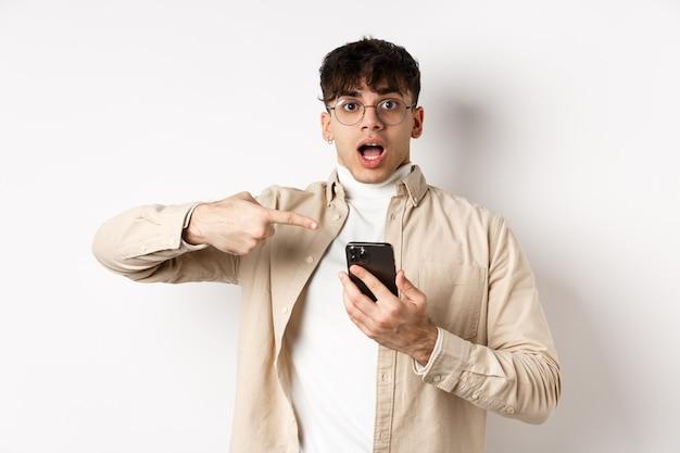 現実の人間。驚いた若い男が携帯電話でオンラインオファーをチェックし、興奮した顔でスマートフォンの画面を指して、白い背景の上に立っています