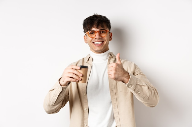 Real people. cheerful smiling guy in glasses drinking coffee and showing thumb up, recommending cafe, standing on white wall.