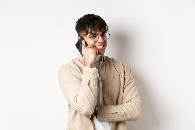 実在の人々の概念。携帯電話で話しているハンサムな現代人は、脇を見て、耳の近くにスマートフォンを持って、白い壁に立っています。