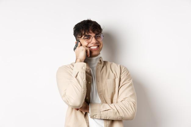 実在の人々の概念。携帯電話で話している幸せな若い男、脇を見て、耳の近くにスマートフォンを持って、白い壁に立っています。