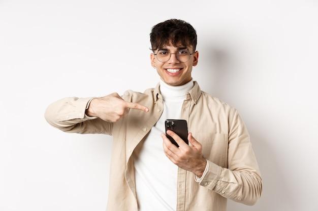 現実の人間。スマートフォンの画面に指を指し、オンラインプロモーションを表示し、白い背景の上に立って眼鏡をかけてハンサムな若い男