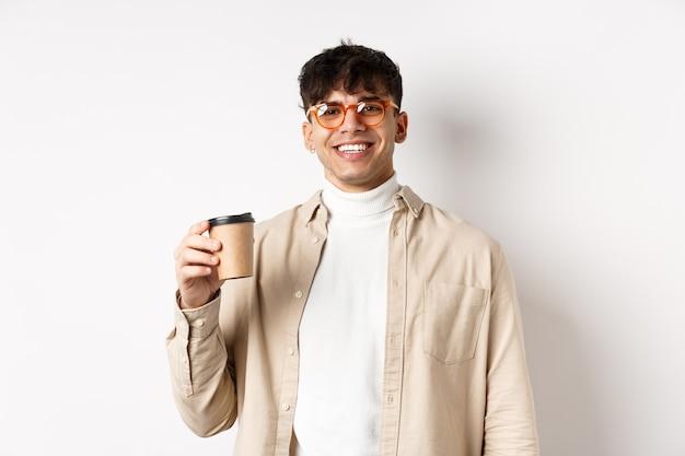 Настоящие люди. счастливый молодой человек пьет кофе из бумажного стаканчика, заказывает еду на вынос в любимом кафе, улыбаясь, белая стена.