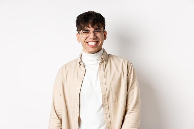 Настоящие люди. естественный портрет счастливого парня, улыбающегося и смеющегося, оптимистично смотрящего в камеру, стоящего в очках на белом фоне