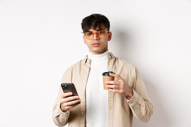 Настоящие люди. стильный битник парень в очках, держа чашку кофе из кафе на вынос и мобильный телефон, стоя на белой стене.