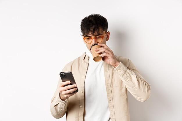 Настоящие люди. молодой человек читает экран смартфона и пьет кофе, глядя на телефон, стоя на белой стене.