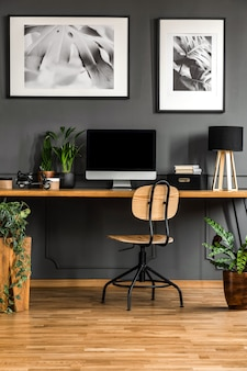 Real photo of a dark, wooden home office interior with empty computer monitor o the desk standing against black wall with molding