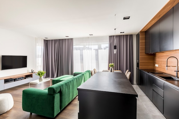Real photo of hotel room interior with green lounge, tv set, windows with drapes and open space kitchen corner