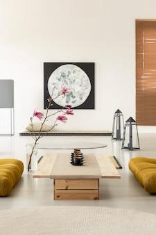 Реальное фото яркого восточного интерьера с рядом чайных чашек на невысоком деревянном столе с желтыми подушками с обеих сторон и украшением из розовых цветов.