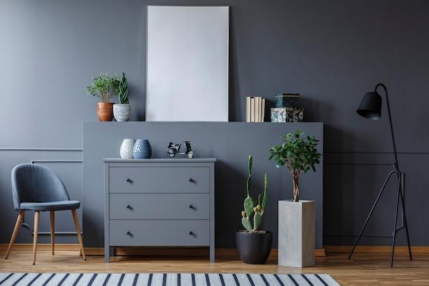 椅子とランプの間に箪笥が立っていて、周りに植物や装飾品が置かれている単色のリビングルームの実際の写真。グラフィックの場所を含むポスターモックアップ