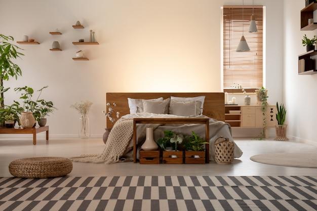 ダブルベッド、縞模様のカーペット、植物、ランプ、背景に空の壁があるエコベッドルームのインテリアの実際の写真。あなたの絵を置きます