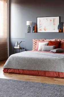 灰色の毛布とクッションが付いたベッドの後ろのベッドヘッドに黒い壁、ランプ、ポスターが付いた、暗くてエレガントな寝室のインテリアの実際の写真