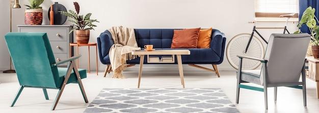 パターン化された敷物の隣に立って、オレンジ色の枕とカラフルなリビングルームのインテリアに木製のテーブルが付いた青いソファに面している緑と灰色のアームチェアの実際の写真