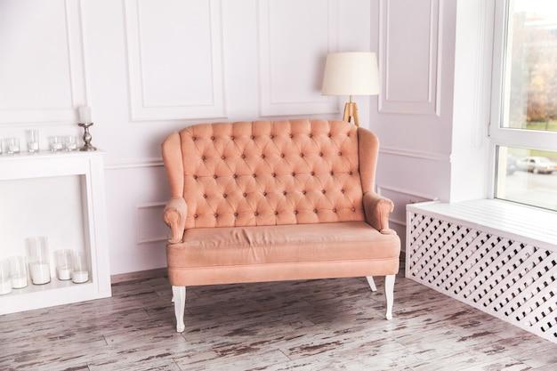 Pich 소파와 흰색 거실 인테리어의 실제 사진. 안락 의자를위한 장소