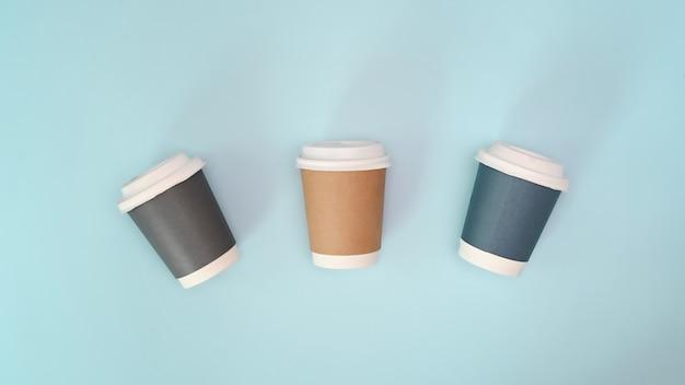 Настоящий бумажный стаканчик для фотографий на вынос экологически чистый на синем фоне.
