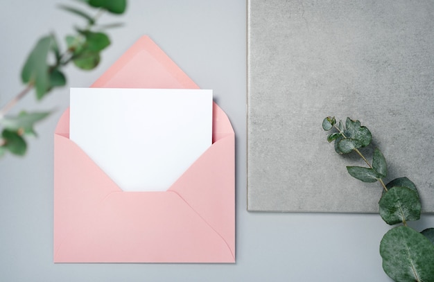 本物の写真。ユーカリの枝が付いているピンクの封筒の正方形の招待カードのモックアップ。コピースペース、明るい灰色の背景の上面図。ブランディングと広告のためのテンプレート