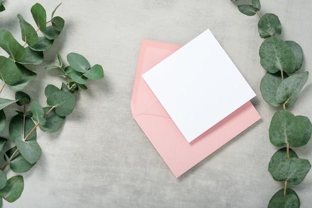 本物の写真。ユーカリの枝が付いているピンクの封筒の正方形の招待カードのモックアップ。コピースペース、ライトグレーのコンクリートの背景を持つ上面図。ブランディングと広告のためのテンプレート
