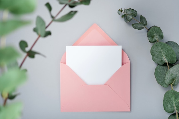 Real photo. pink envelope square invitation card mockup with a eucalyptus branch. top view with copy space, light gray background. template for branding and advertising