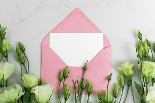 Real photo. pink envelope square invitation card mockup with a eustoma flowers. top view with copy space, light gray marble background. template for branding and advertising.