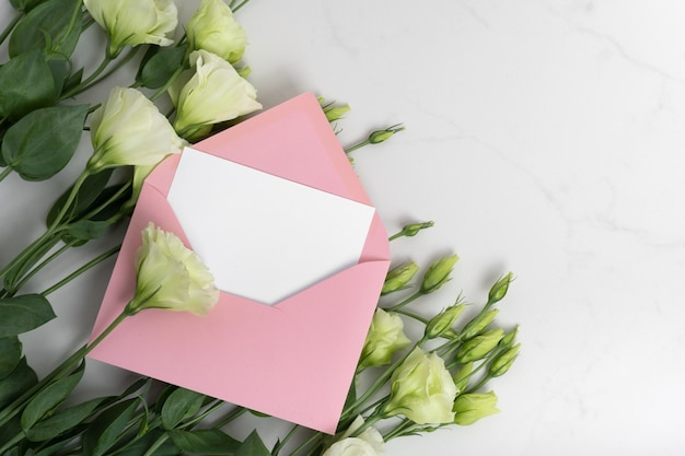 Real photo. pink envelope square invitation card mockup with a eustoma flowers. top view with copy space, light gray marble background. template for branding and advertising