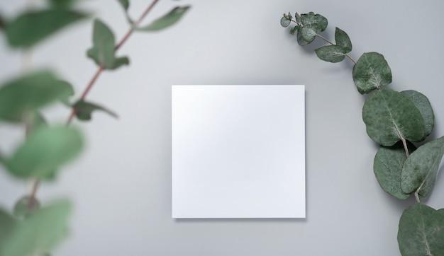 本物の写真。ユーカリの枝が付いている正方形の招待状のモックアップ。コピースペース、明るい灰色の背景の上面図。ブランディングと広告のためのテンプレート