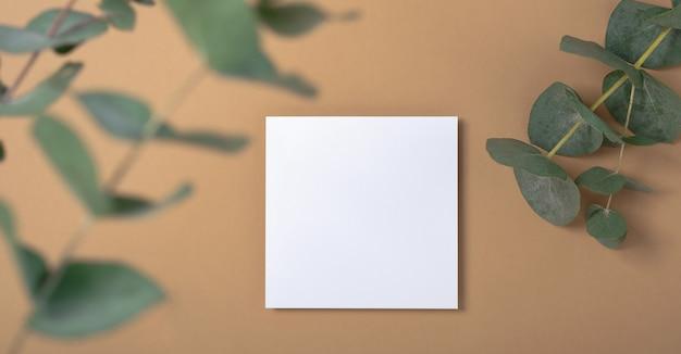 本物の写真。ユーカリの枝が付いた正方形の招待状のモックアップ。コピースペース、パステルベージュの背景を持つ上面図。ブランディングと広告のためのテンプレート。