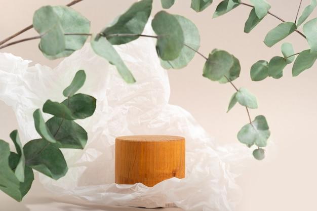 실제 사진. 유칼립투스 나뭇가지의 그림자가 있는 나무 연단, 단단한 빛. 에코 스타일의 화장품에 대한 베이지색 배경. 모형. 구겨진 양피지