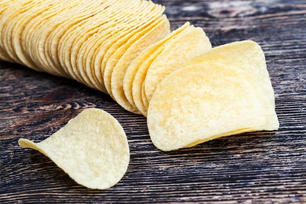 Настоящие картофельные чипсы, желтые золотые чипсы крупным планом, калорийная еда, настоящие и хрустящие чипсы