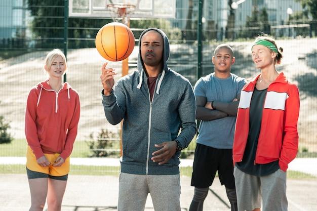진짜 전문가. 공으로 자신의 기술을 보여 주면서 팀 앞에 서있는 즐거운 좋은 남자