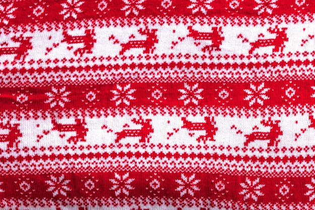 Real red knitted background with white christmas deer and snowflakes.