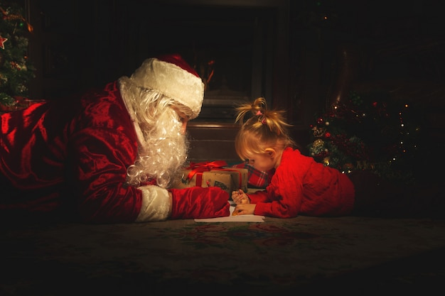 Real santa claus is playing with children near the christmas tree.