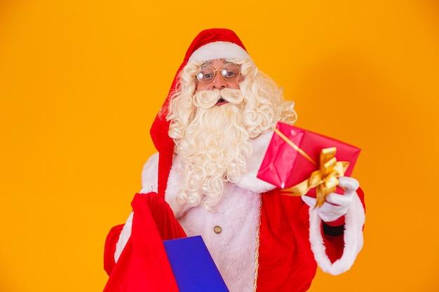さまざまなクリスマスプレゼントとバッグを保持している黄色の背景に本物のサンタクロース。