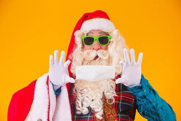 Настоящий санта-клаус на желтом фоне, держа в руках защитную маску от covid19. рождество с социальной дистанцией. covid-19