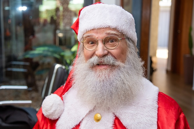 The real santa claus, wearing glasses, gloves and a hat looking straight into the camera. close up. the real santa claus looking at camera