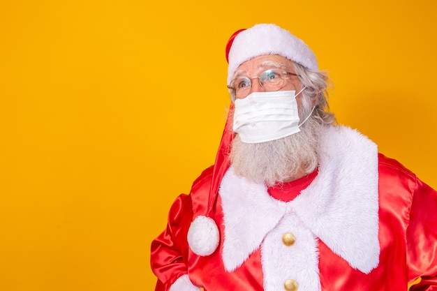 노란색 배경을 가진 진짜 산타클로스, 보호용 마스크, 안경, 모자를 쓰고 있습니다. 사회적 거리두기가 있는 크리스마스. 코로나 19